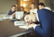 Businessman sleeping in conference room meeting - CAIF06640