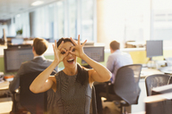 Portrait of playful businesswoman pretending to wear glasses in office - CAIF06643