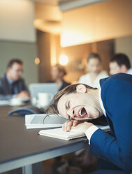 Tired businessman yawning and laying on conference table - CAIF06646