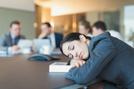 Businesswoman sleeping in conference room meeting - CAIF06649