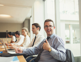 Portrait of confident businessman gesturing thumbs-up in conference room meeting - CAIF06655