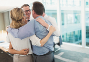 Smiling business people hugging in huddle in conference room - CAIF06658