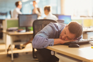 Businessman sleeping on desk in office - CAIF06664