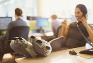 Businesswoman wearing wolf paw slippers with feet up on desk talking on telephone - CAIF06676