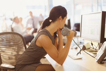 Businesswoman doing biceps curls with dumbbell and talking on telephone at computer in office - CAIF06682