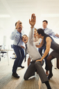 Exuberant business people celebrating and dancing in office - CAIF06685