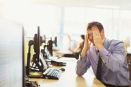 Stressed businessman with head in hands at office desk - CAIF06688