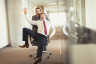 Playful businessman pushing colleague down corridor in office chair - CAIF06694