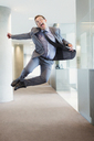 Exuberant businessman jumping for joy in office corridor - CAIF06697