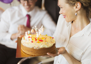 Smiling businesswoman holding birthday cake with candles - CAIF06706