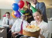 Portrait smiling businesswoman holding birthday cake with colleagues in background - CAIF06709