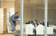 Businessman with megaphone on top of chair in conference room meeting - CAIF06712