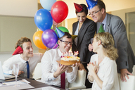 Colleagues presenting businesswoman with birthday cake in conference room - CAIF06715
