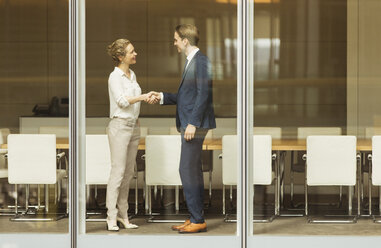 Businessman and businesswoman handshaking at conference room window - CAIF06727