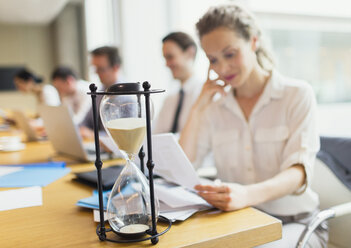 Hourglass in front of businesswoman reviewing paperwork in conference room - CAIF06730