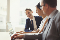 Smiling business people using laptop in conference room - CAIF06733