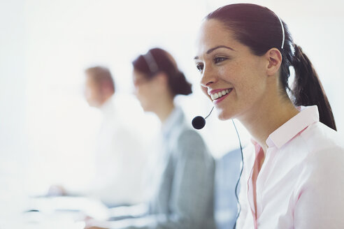 Smiling businesswoman talking on the phone with headset - CAIF06745