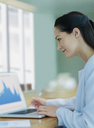 Businesswoman working at laptop in conference room - CAIF06754