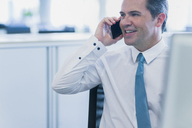 Smiling businessman talking on cell phone in office - CAIF06760