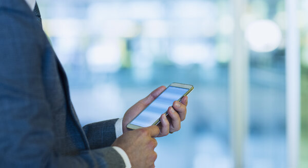 Businessman using cell phone in office - CAIF06763