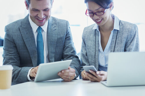 Businessman and businesswoman using digital tablet and cell phone in office - CAIF06772