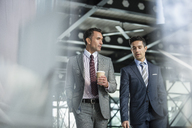 Corporate businessmen walking with coffee - CAIF06775