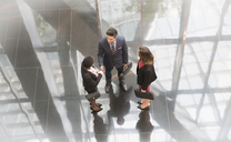 Corporate business people talking in modern office lobby - CAIF06814