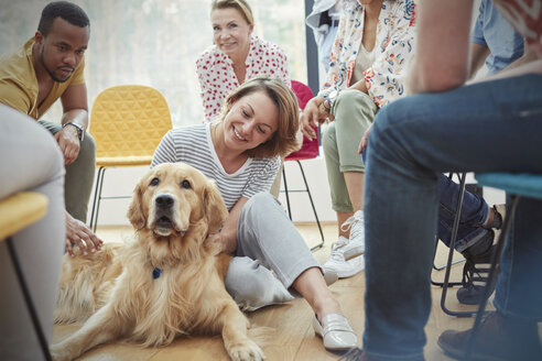 Woman petting dog in group therapy session - CAIF06853