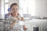 Portrait smiling businesswoman drinking coffee in office - CAIF06874