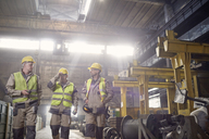 Steelworkers walking and talking in steel mill - CAIF06907