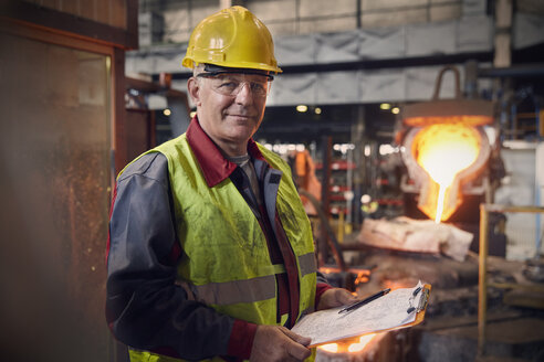 Portrait confident steelworker supervisor with clipboard in steel mill - CAIF06910