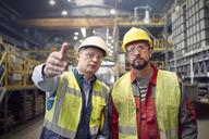 Steelworkers talking, gesturing in steel mill - CAIF06922