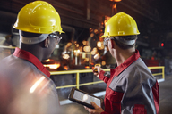 Supervisor and steel worker with digital tablet working in steel mill - CAIF06925