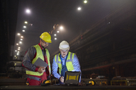 Steelworkers using laptop in dark steel mill - CAIF06928