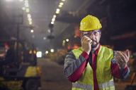 Steelworker talking, using walkie-talkie in steel mill - CAIF06946