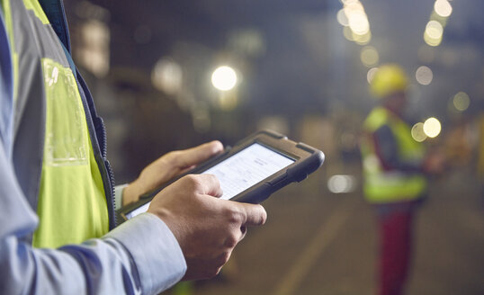 Close up steelworker supervisor using digital tablet in steel mill - CAIF06952