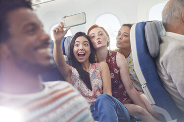 Playful young friends with camera phone taking selfie on airplane - CAIF06988