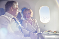 Smiling mature couple eating and talking in first class on airplane - CAIF06991
