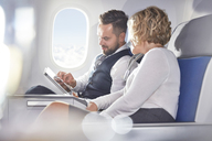 Businessman and businesswoman using digital tablet on airplane - CAIF07003