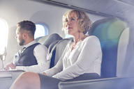 Businesswoman sitting in first class on airplane - CAIF07012