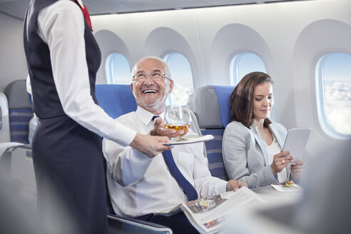 Flight attendant serving whiskey to smiling businessman riding in first class on airplane - CAIF07015