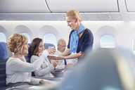 Flight attendant serving drink to woman on airplane - CAIF07024