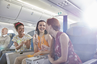 Young women friends drinking champagne in first class on airplane - CAIF07027