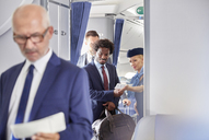 Flight attendant helping businessman with boarding pass on airplane - CAIF07033
