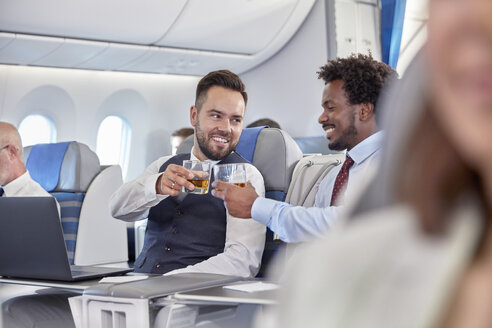 Businessmen toasting whiskey glasses in first class on airplane - CAIF07036