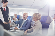 Flight attendant serving champagne to mature couple in first class on airplane - CAIF07051