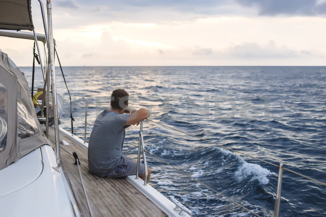 Indonesia, Lombok island, man sitting on deck of a sailing boat - KNTF01081