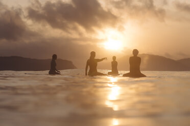 Indonesia, Lombok, group of surfers sitting on surfboards at sunset - KNTF01084