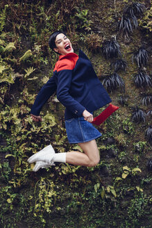 Portrait of fashionable young woman jumping in the air in front of Living Wall - JSMF00085