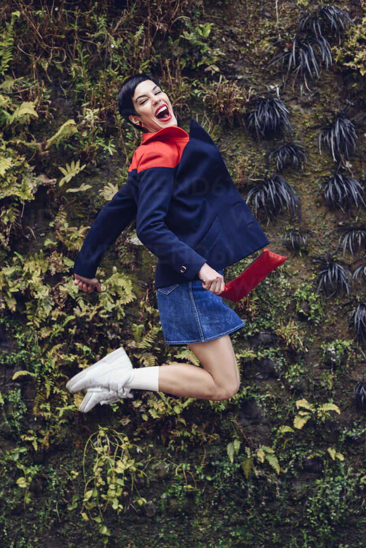 Portrait of fashionable young woman jumping in the air in front of Living Wall - JSMF00085 - Javier Sánchez Mingorance/Westend61